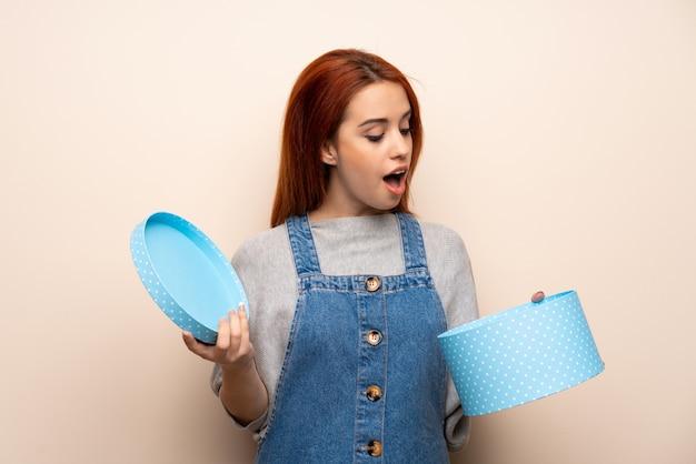 Giovane donna di redhead isolata sopra tenendo un regalo in mano Foto Premium