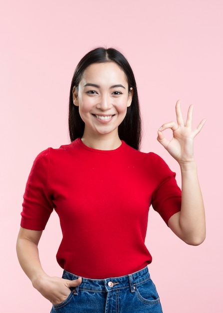 Giovane donna di smiley che mostra segno giusto Foto Gratuite