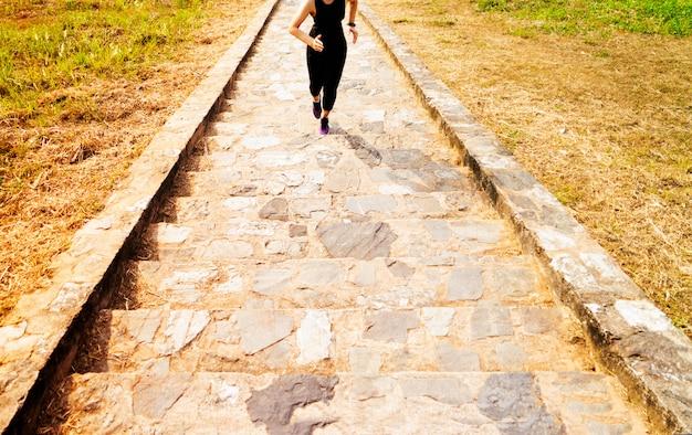 Giovane donna di sport che corre all'aperto di sopra su cielo blu Foto Premium
