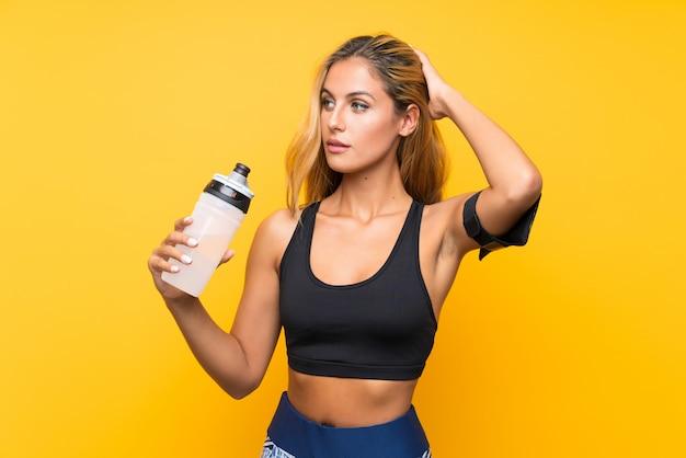 Giovane donna di sport con una bottiglia di acqua sopra la parete isolata Foto Premium