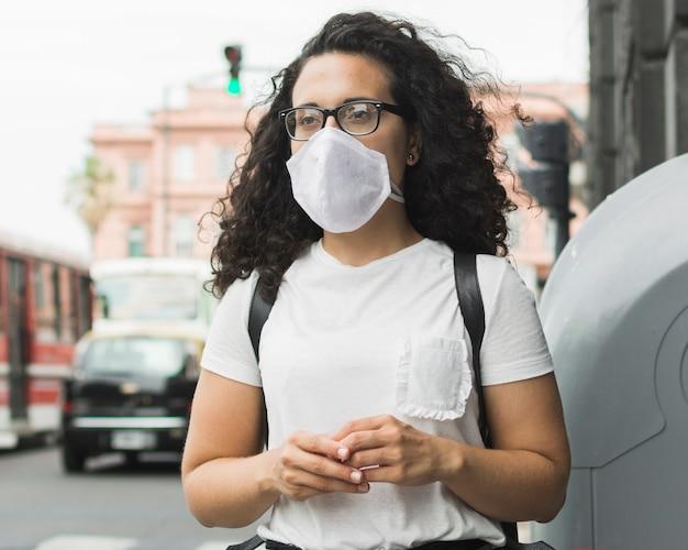 Giovane donna di vista frontale che indossa una maschera medica fuori Foto Gratuite