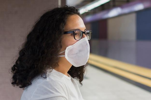 Giovane donna di vista laterale con l'attesa medica della maschera Foto Gratuite