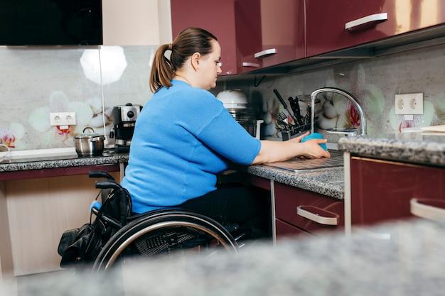 Giovane donna disabile in sedia a rotelle che lava i piatti nella cucina appositamente attrezzata Foto Premium