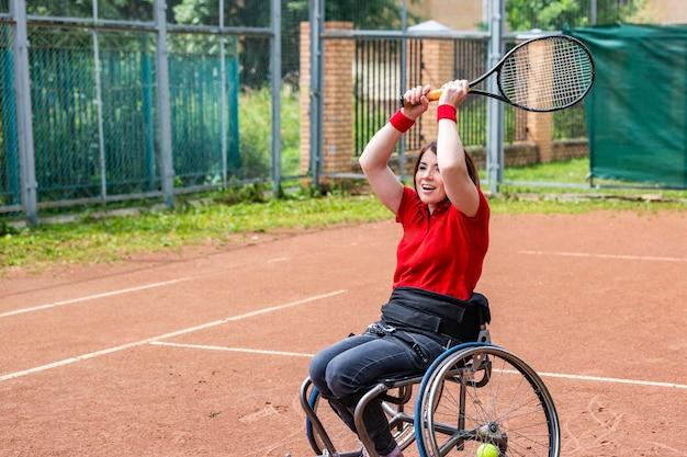Giovane donna disabile sulla sedia a rotelle che gioca a tennis sul campo da tennis. Foto Premium