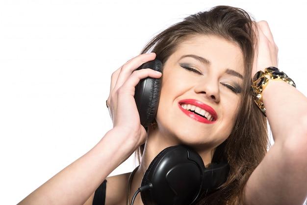 Giovane donna dj che gode della musica in cuffia. Foto Premium