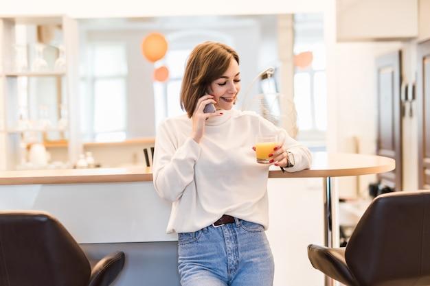 Giovane donna è in piedi vicino al bar sedia in cucina a parlare al telefono e in possesso di un bicchiere con succo d'arancia Foto Gratuite