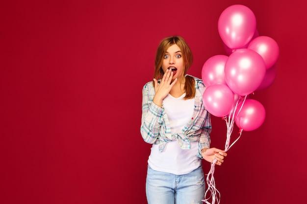 Giovane donna emozionante che posa con gli aerostati rosa Foto Gratuite
