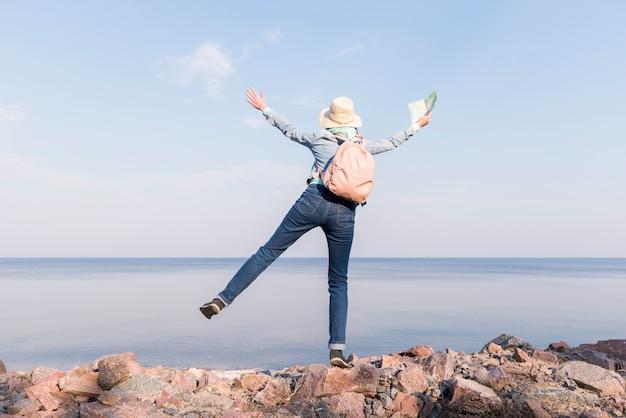 Giovane donna emozionante che sta sopra la mappa tenuta della roccia a disposizione che trascura il mare contro il cielo blu Foto Gratuite