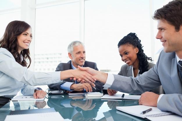 Giovane donna esecutiva e un collega che stringe le mani nel corso di una riunione Foto Premium