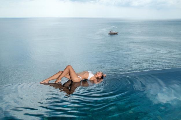Giovane donna esile che posa sul bordo della piscina a sfioro di lusso. barca in mare. Foto Premium