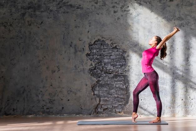 Giovane donna esile che pratica allungando esercizio contro la parete esposta all'aria Foto Gratuite