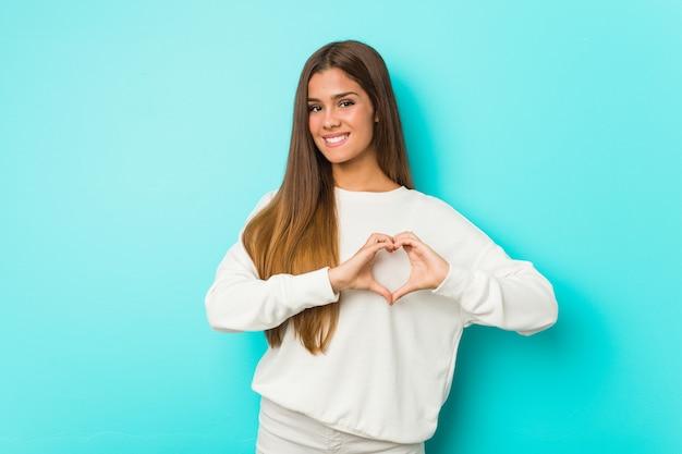 Giovane donna esile che sorride e che mostra una forma del cuore con le mani. Foto Premium