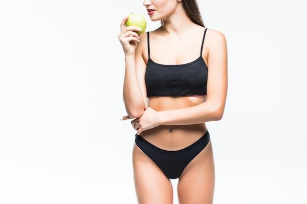 Giovane donna esile che tiene mela verde. isolato sul muro bianco. concetto di cibo sano e controllo del peso in eccesso. Foto Gratuite
