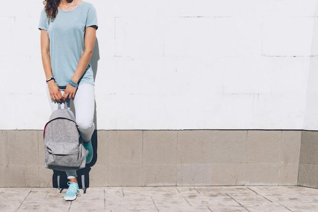 Giovane donna esile in jeans e t-shirt in piedi contro un muro bianco con uno zaino in mano Foto Premium