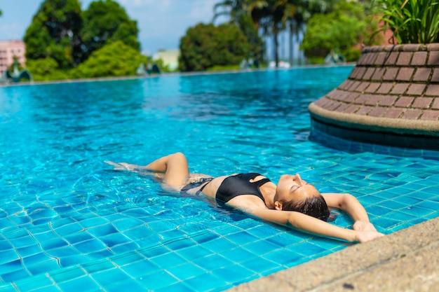 Giovane donna esile sexy che si rilassa nella piscina tropicale con acqua blu di cristallo nel giorno di estate caldo Foto Premium