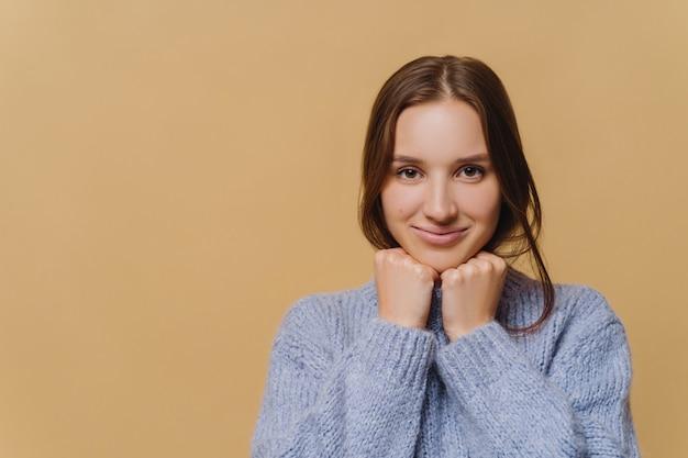 Giovane donna europea con un trucco minimale, capelli scuri, vestita in maglione invernale, tiene le mani sotto il mento, ha un sorriso affascinante, si erge su sfondo marrone, copia spazio per i tuoi contenuti pubblicitari Foto Premium