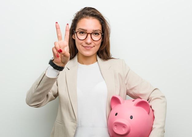 Giovane donna europea di affari che tiene un porcellino salvadanaio che mostra numero due con le dita. Foto Premium