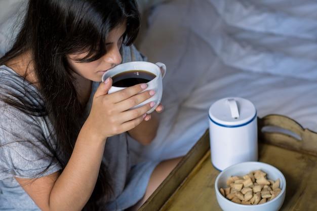 Giovane donna facendo colazione a letto Foto Premium