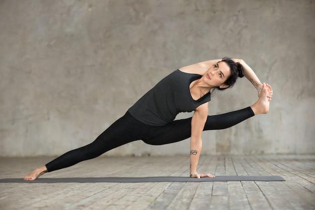 Giovane donna facendo esercizio visvamitrasana Foto Gratuite