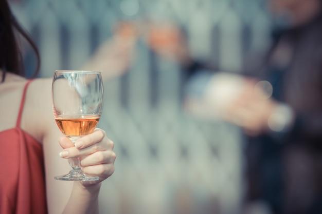 Giovane donna felice bere tenendo e bere un bicchiere di alcol al bar notturno o night club Foto Premium