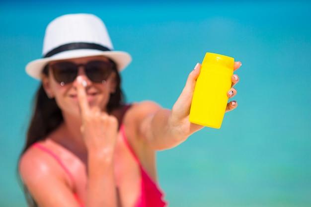 Giovane donna felice che applica lozione solare sul suo naso sulla spiaggia bianca Foto Premium
