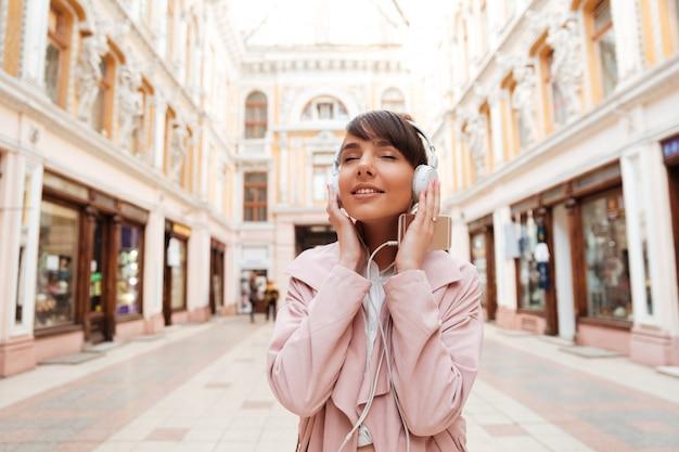 Giovane donna felice che gode ascoltando la musica su una strada cittadina Foto Gratuite