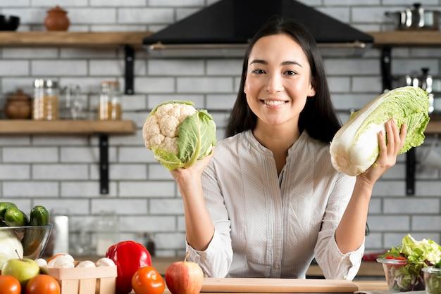 Giovane donna felice che mostra gli ortaggi freschi in cucina Foto Gratuite