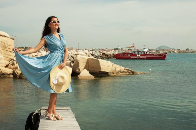Giovane donna felice che posa vicino al mare Foto Premium
