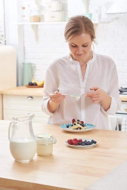Giovane donna felice che prepara gli spuntini saporiti alla luce del tavolo da cucina di mattina Foto Premium