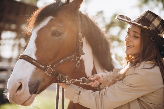 Giovane donna felice con cavallo al ranch Foto Gratuite