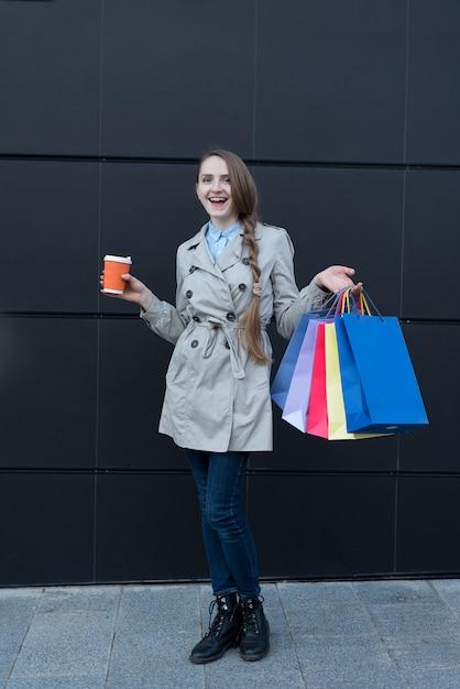 Giovane donna felice con i sacchetti variopinti e la tazza di carta. muro di strada nero Foto Premium