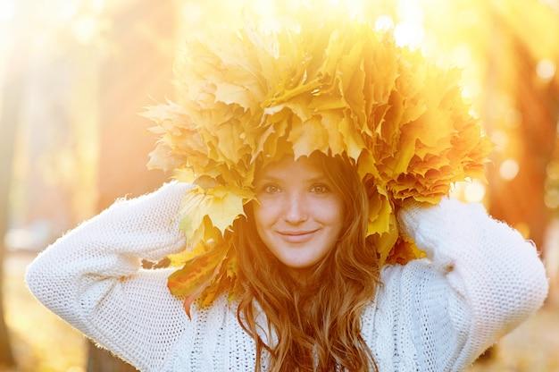 Giovane donna felice con una corona di foglie gialle che cammina nel parco Foto Premium