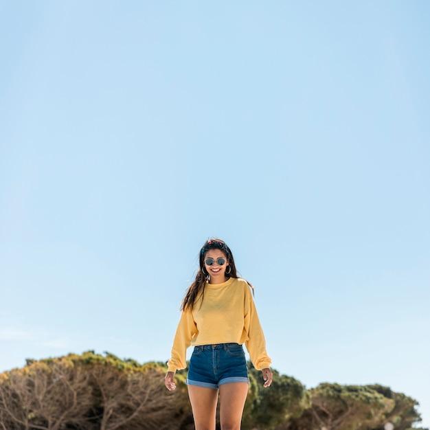 Giovane donna felice contro cielo blu in natura Foto Gratuite