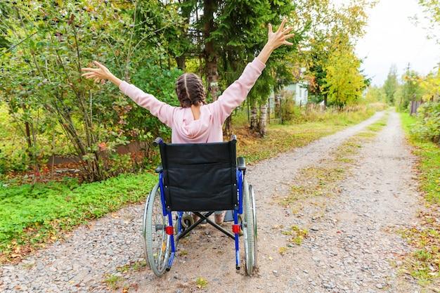 Giovane donna felice di handicap in sedia a rotelle sulla strada nel parco dell'ospedale che gode della libertà. ragazza paralizzata in sedia invalida per disabili all'aperto in natura. concetto di riabilitazione. Foto Premium