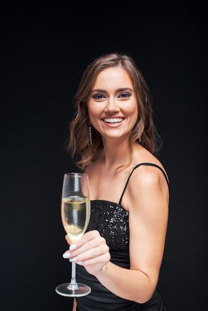 Giovane donna felice in abito elegante con un bicchiere di champagne alla festa. Foto Premium