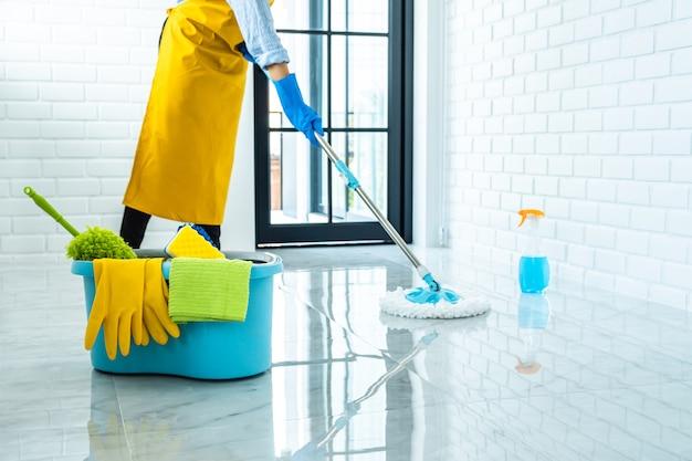 Giovane donna felice in gomma blu facendo uso di zazzera mentre pulendo sul pavimento a casa Foto Premium