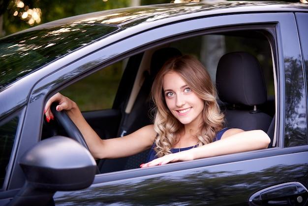 Giovane donna felice in un'automobile nera. Foto Premium