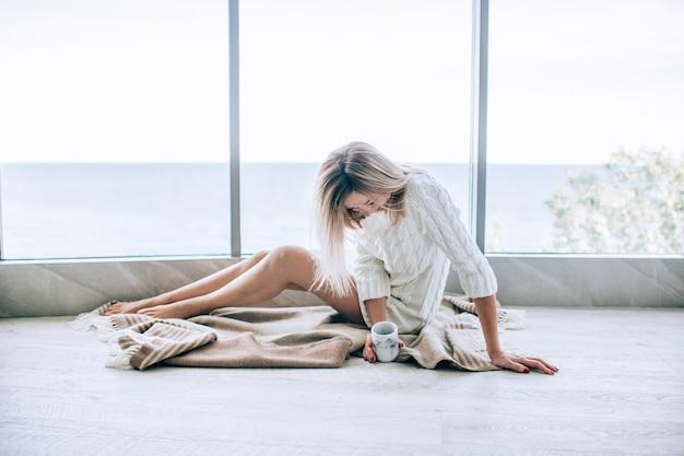 Giovane donna felice in un vestito lavorato a maglia bianco che gode della vista del mare vicino alla grande finestra con la tazza di tè e la risata. finestra panoramica. rivestimenti per pavimenti. Foto Premium