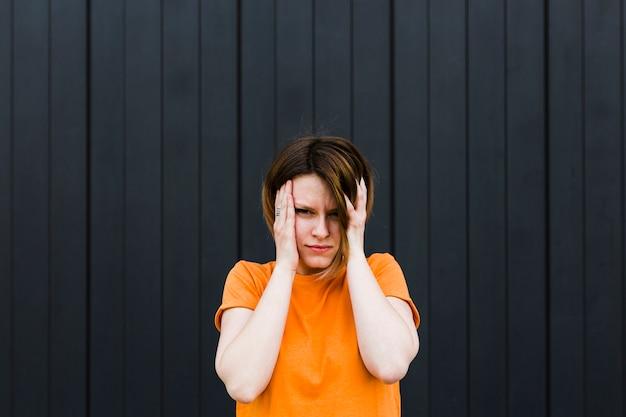 Giovane donna frustrata contro il contesto a strisce nero Foto Gratuite