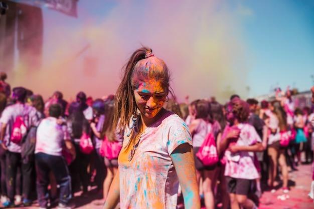 Giovane donna godendo con colori holi nella folla Foto Gratuite