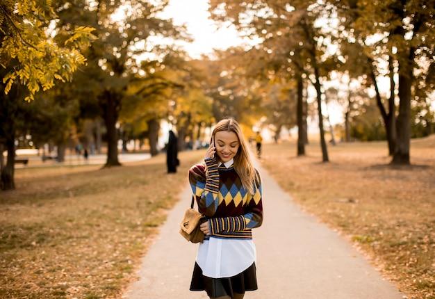 Giovane donna graziosa che cammina nel parco di autunno e che per mezzo di un telefono cellulare Foto Premium
