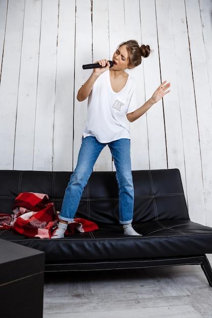 Giovane donna graziosa che canta in microfono sul sofà a casa. Foto Gratuite