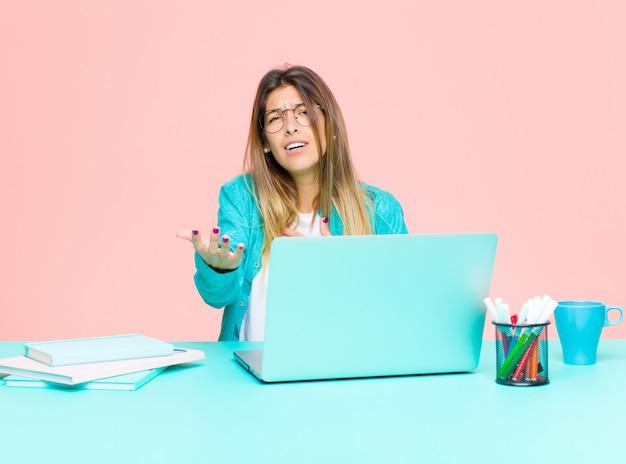 Giovane donna graziosa che lavora con un computer portatile che si sente felice e innamorato Foto Premium