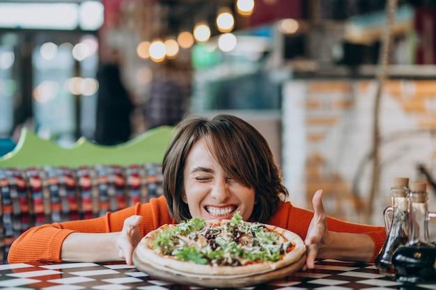 Giovane donna graziosa che mangia pizza al bar della pizza Foto Gratuite
