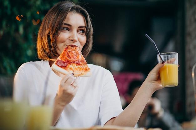 Giovane donna graziosa che mangia pizza in un bar Foto Gratuite