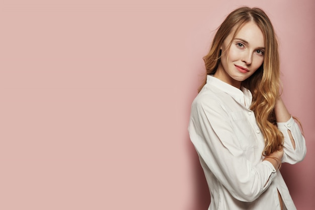 Giovane donna graziosa che posa sul fondo rosa Foto Gratuite