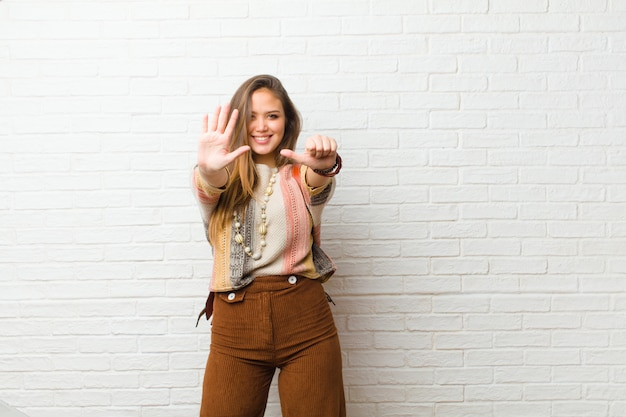 Giovane donna graziosa che sorride e che sembra amichevole, mostrando numero sei o sesto con la mano in avanti, conto alla rovescia Foto Premium