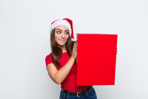 Giovane donna graziosa con cappello santa. concetto di natale. Foto Premium