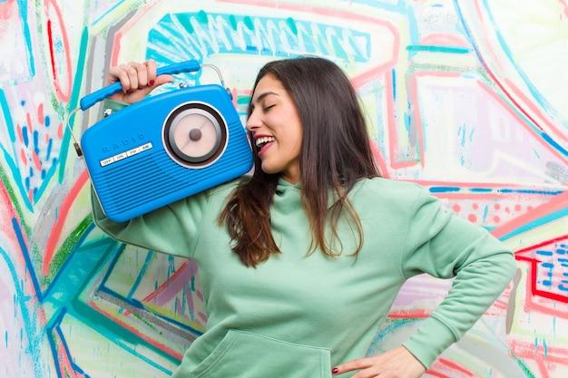 Giovane donna graziosa con una radio vintage contro il muro di graffiti Foto Premium
