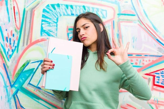 Giovane donna graziosa contro il muro di graffiti Foto Premium